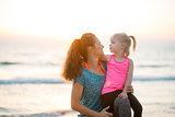 Young fit mother smiling with daughter on her knee on beach