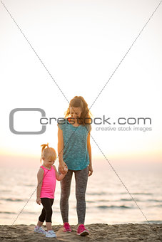Fit young mother and daughter walking and holding hands on beach
