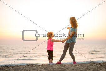 Fit young mother and daughter on the beach, looking out to sea