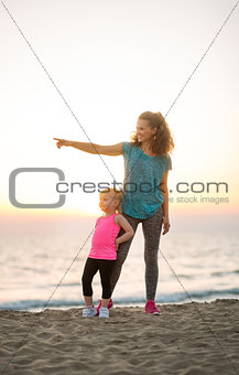 Fit young mother pointing into distance for daughter on beach
