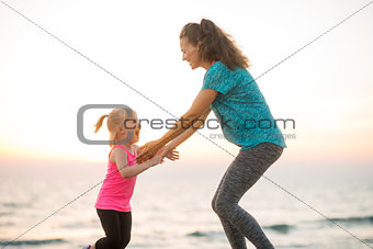 Fit young mother and daughter playing on the beach at sunset
