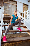 Woman runner sitting on wooden steps of a beach hut