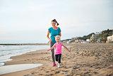 Fit, happy mother running behind young daughter on the beach