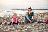 Fit young mother and daughter sitting on beach stretching
