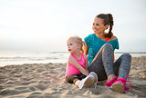 Smiling, fit mother sitting next to young daughter on the sand