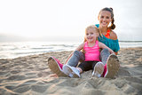 Mother and daughter in workout gear sitting together on beach