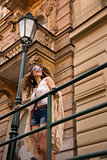 Longhaired hippy girl with sunglasses stands near old town stree