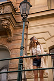 Longhaired hippy lady with sunglasses near old town streelight