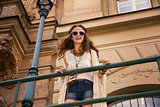 Longhaired boho chic with sunglasses near old town streetlight