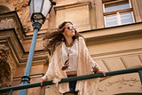 Longhaired bohemian girl with sunglasses near old town streetlig