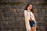 happy boho young woman near stone wall talking cell phone