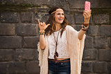 happy boho young woman near stone wall making selfie