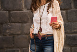 closeup on boho young woman near stone wall writing sms