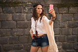 bohemian young woman near stone wall making selfie