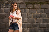 smiling boho young woman near stone wall looking on copy space