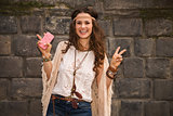 happy boho young woman near stone wall showing victory gesture