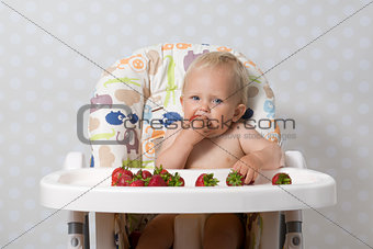 Baby girl eating strawberries