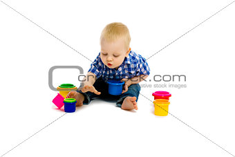 baby boy on a white floor with toys
