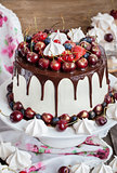 Cake decorated with chocolate, meringues and fresh berries