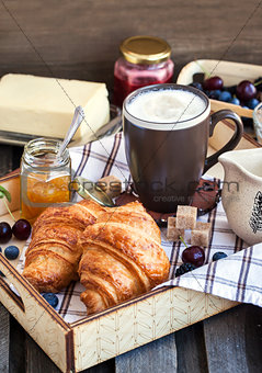 Breakfast with croissants, cappuccino and jam