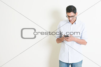 Casual business Indian male using smartphone