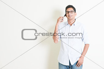 Casual business Indian male talking on smartphone