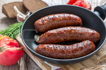 Grilled sausages in frying pan and a ripe tomato.