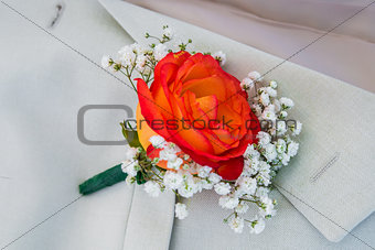 boutonniere of roses in the men's jacket