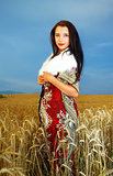 Young woman with ornamental dress and white fur standing on a wheat field with sunset. Natural background