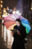 Brunette woman using tablet on the street on rainy day