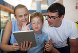 Parents and son with tablet PC at the airport