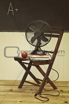 Old fan with apple and books on chair