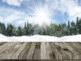 Wooden table with defocussed christmas snowy landscape in the ba
