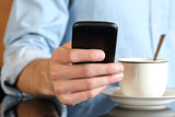 Close up of a hand using a smart phone at breakfast