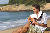 Handsome man playing classic guitar on the beach