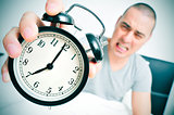 angry young man in bed holds his alarm clock