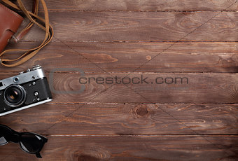 Camera and sunglasses on wooden desk