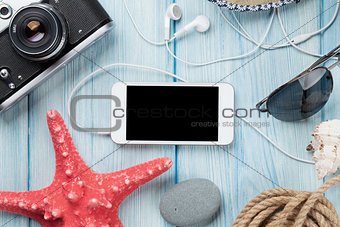Smartphone and camera on table with starfish and shells
