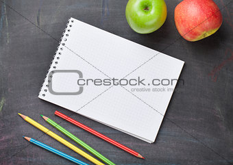 Blank notepad, pencils and apples on blackboard