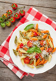 Colorful penne pasta with tomatoes and basil