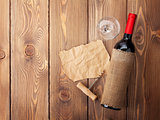 Red wine bottle, glass and corkscrew on wooden table