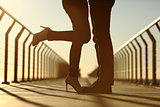 Couple legs silhouette hugging with love in a bridge