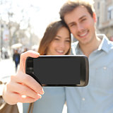 Couple making a selfie photo with a smartphone and showing screen