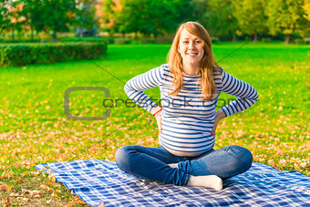 Pregnant woman resting on a plaid autumn park