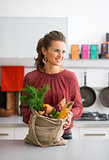 Smiling woman holding bag of autumn vegetables in kitchen