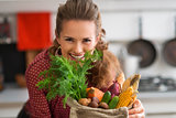 Smiling woman looking over a burlap sac of fresh fall vegetables