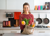 Smiling woman with bag of fresh produce holding up an apple