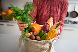 Closeup of fall vegetables and nuts in burlap bag held by woman