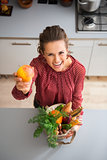 Happy woman holding up apple while holding fall vegetables