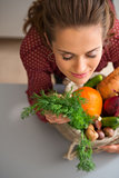 Woman with eyes closed smelling fresh fall vegetables